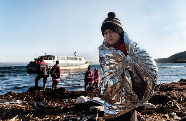 A boy wearing an emergency blanket to warm himself, arrives, with other refugees and migrants, on the Greek island of Lesbos, on October 27, 2015, after crossing the Aegean sea from Turkey. The bodies of two migrants were found on the Greek islands of Lesbos and Chios on October 26, after accidents aboard two boats bound for Europe, according to Greek police. Despite worsening weather at the onset of winter that has made the already hazardous sea voyage from Turkey to Greece even more dangerous, a record 48,000 refugees and migrants arrived last week in Greece, said the International Organization for Migration. AFP PHOTO / ARIS MESSINIS (Photo credit should read ARIS MESSINIS/AFP/Getty Images)
